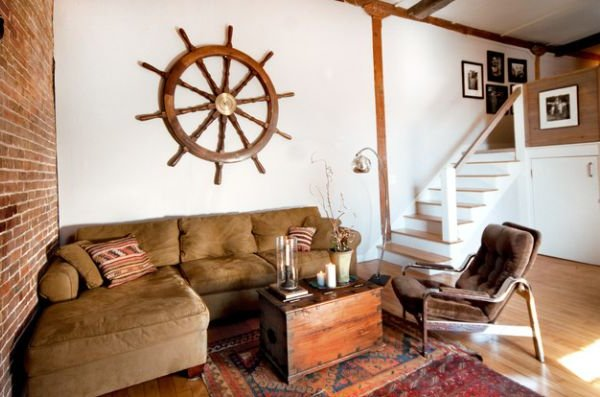 salón con sillón marrón, paredes blancas y timón en la pared