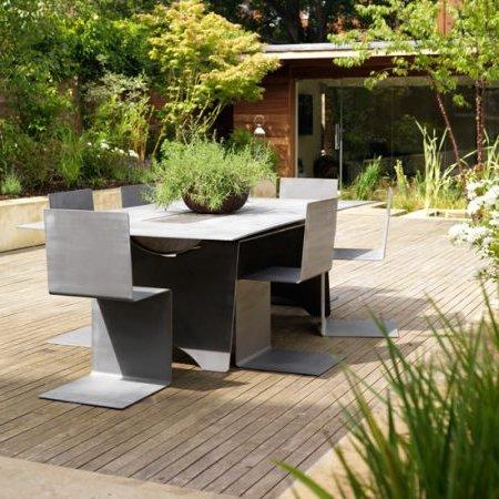 jardin con canteros en el perímetro, mesa y sillas en suelo de madera central