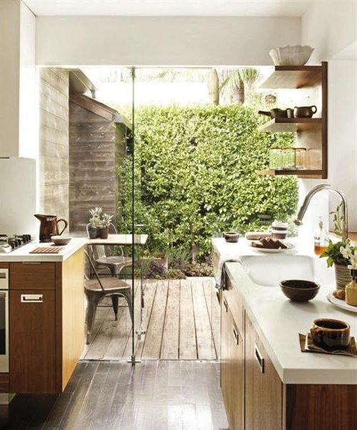 Cocina con armarios de madera y ventana grande al jardín verde