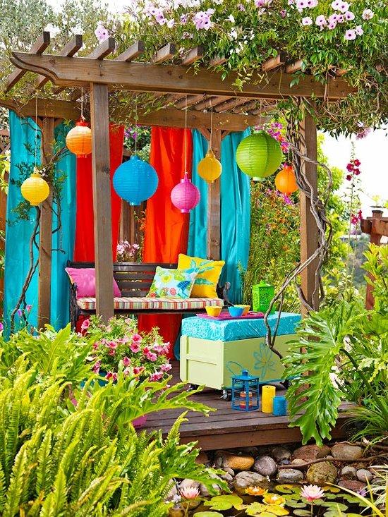 decoración colorida de jardín con pérgola, lámparas de colores y bancos con cojines