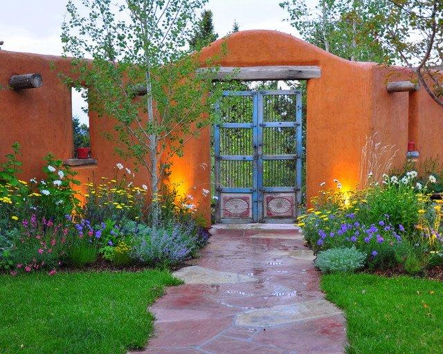 Jardín verde con muros en color naranja y puerta con rejas