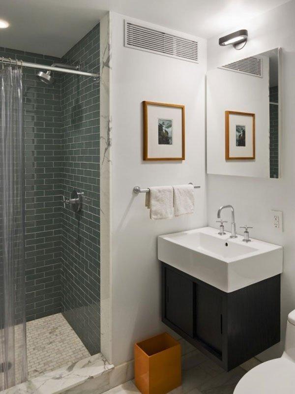Lavabo estiloso de cerámica blanca con mueble debajo en color marrón oscuro. Paredes blancas y ducha de color gris oscuro.
