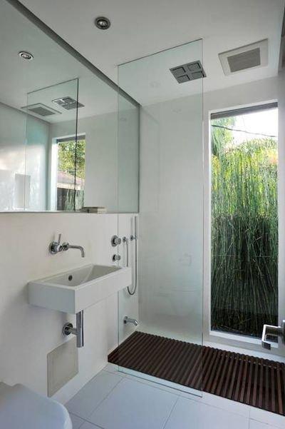 Cuarto de baño de paredes y suelo blancos, con espejo que abarca toda la pared