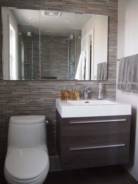 Pared en la que está instalado un lavabo con mueble de madera, inodoro y espejo grande. Azulejos en diferentes tono de marrón y gris