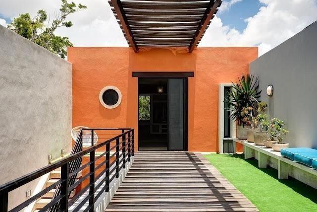 pared exterior color naranja combinada con dos paredes grises cemento