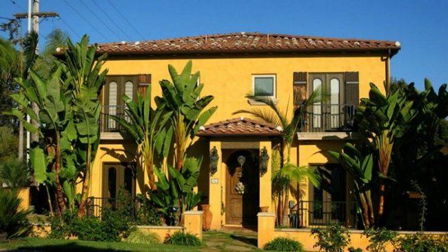 casa con paredes amarillas intensas y aberturas verde oliva