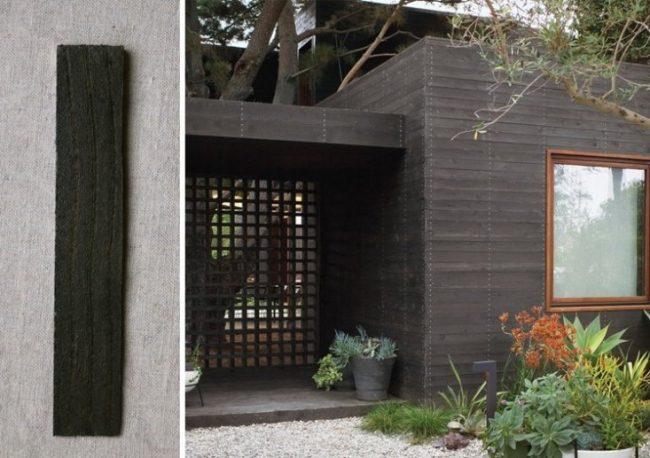 Exterior de casa gris oscuro con marcos de la ventana de madera