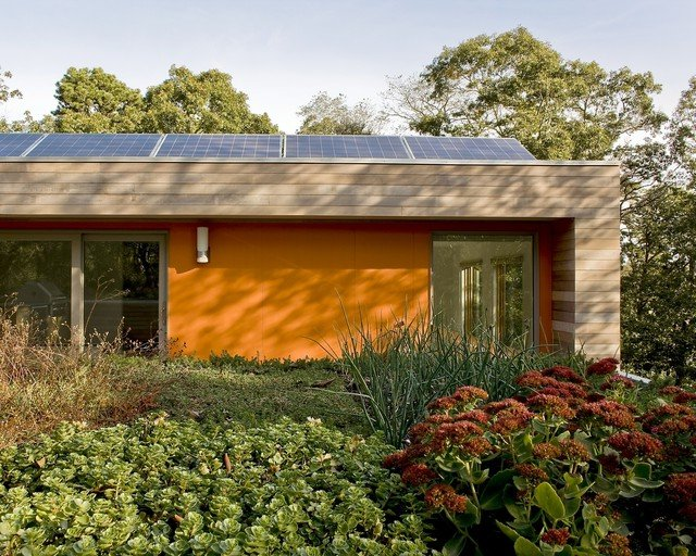 Fachada de color naranja combinada con madera natural