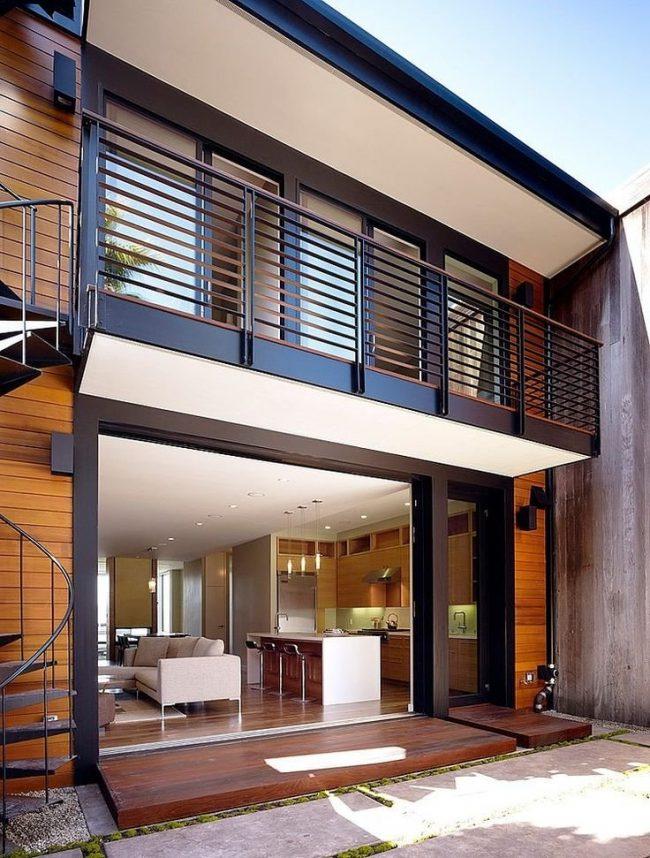Balcón rejas pintadas de negro y detalles de madera
