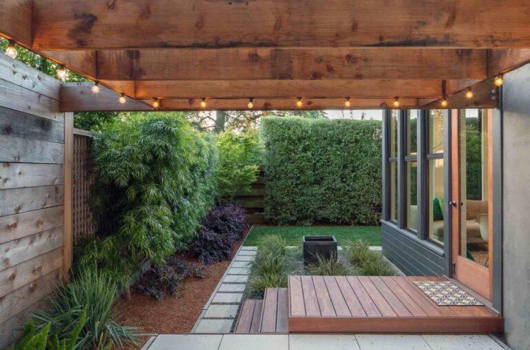patio moderno rodeado de muros, con senderos de cemento y canteros de plantas verdes